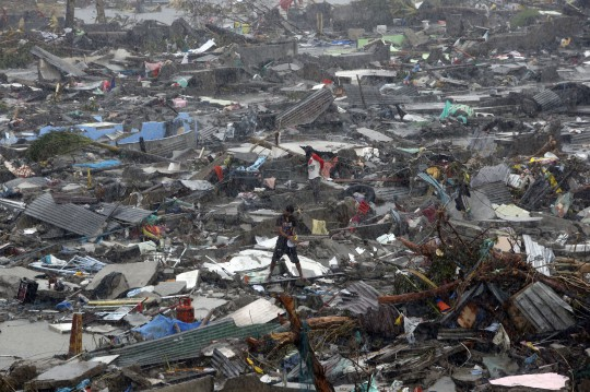 A man stands atop debris as residents salvage belongings from the ruins of their houses after Typhoon Haiyan battered Tacloban city in central Philippines